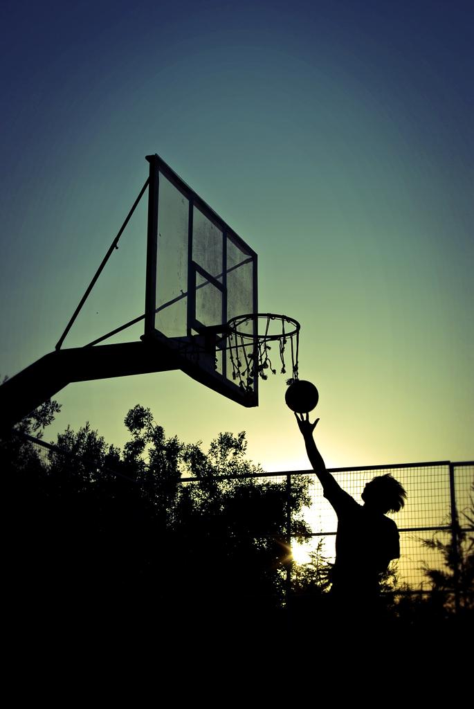 Joueur de basket à contre jour avec le coucher de soleil en fond