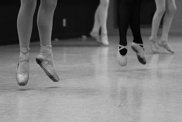 Jambes de danseuses en pleine action avec collants et pointes.