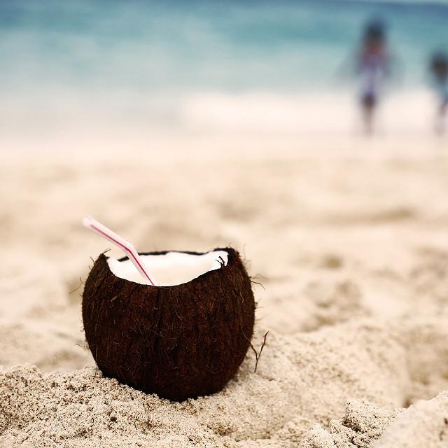 Noix de coco fendue sur la plage, avec une paille.