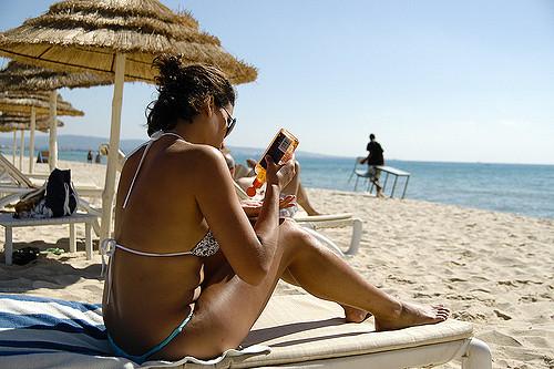 Une femme en maillot de bain bronze sur la plage et se met de l'huile protectrice.