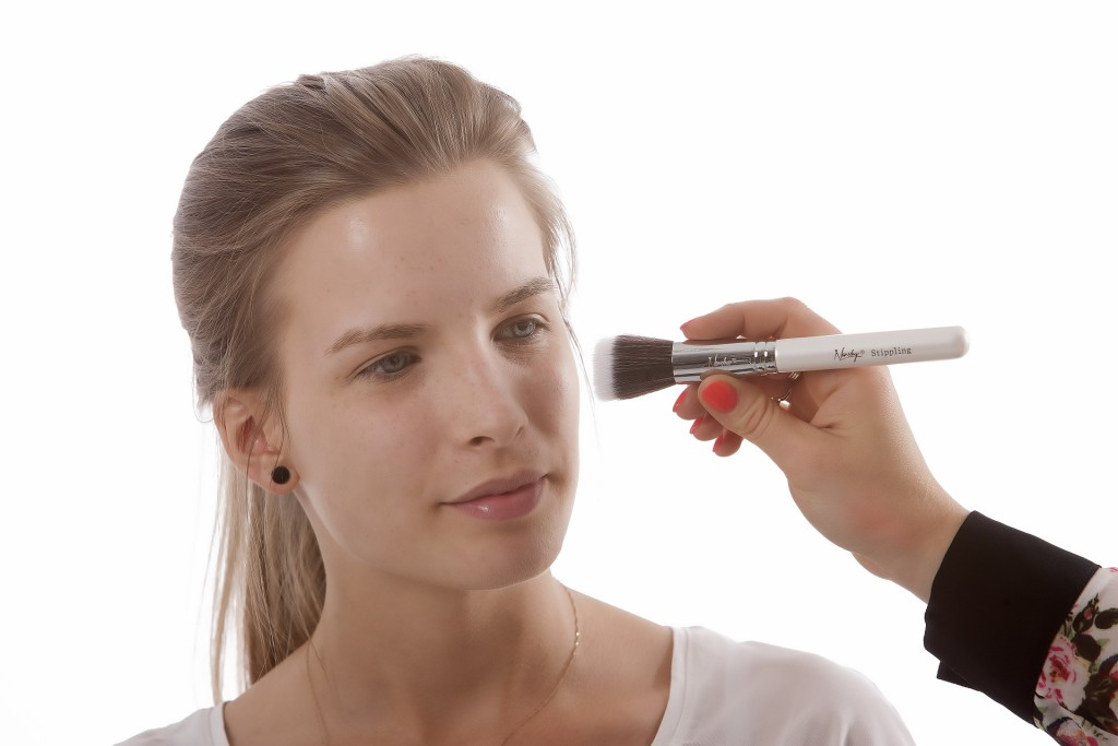Femme se faisant maquiller avec un pinceau.