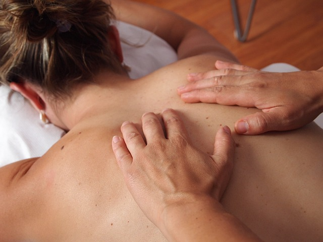 Un ostéopathe masse un dos de femme.