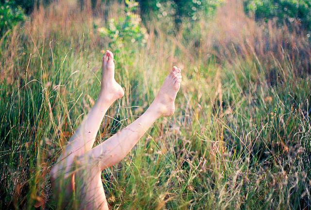 Jeune femme allongée dans l'herbe, les pieds en l'air.