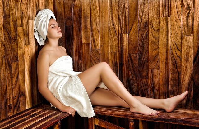 Femme dans un sauna, enroulée dans des serviettes éponges blanches.