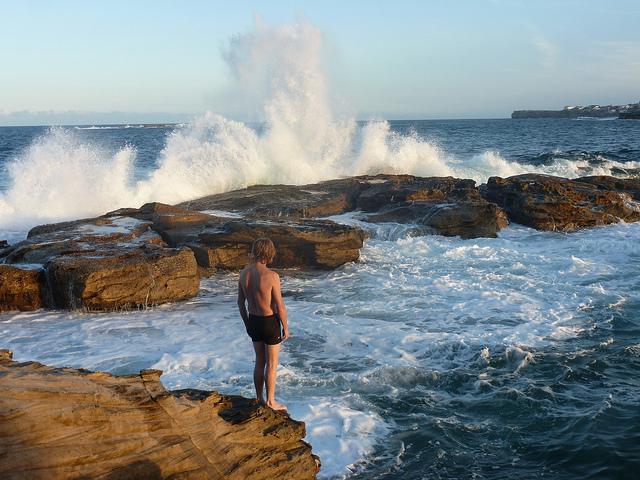 Personne face aux vagues qui se brisent sur des rochers.