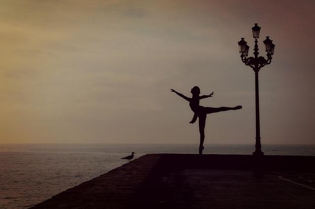 Danseuse classique près de la mer avec coucher de soleil.