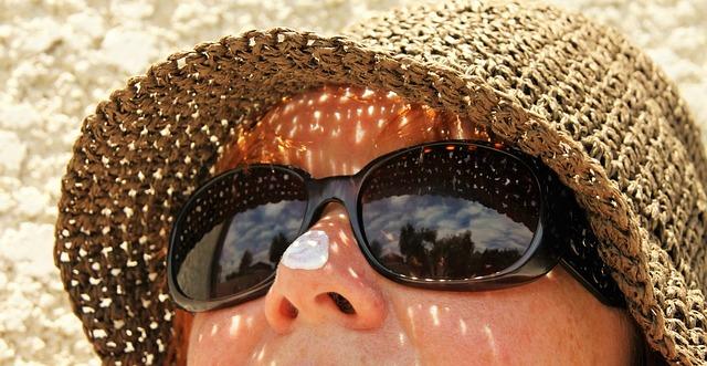 Femme avec lunettes de soleil, chapeau et crème solaire sur le nez.