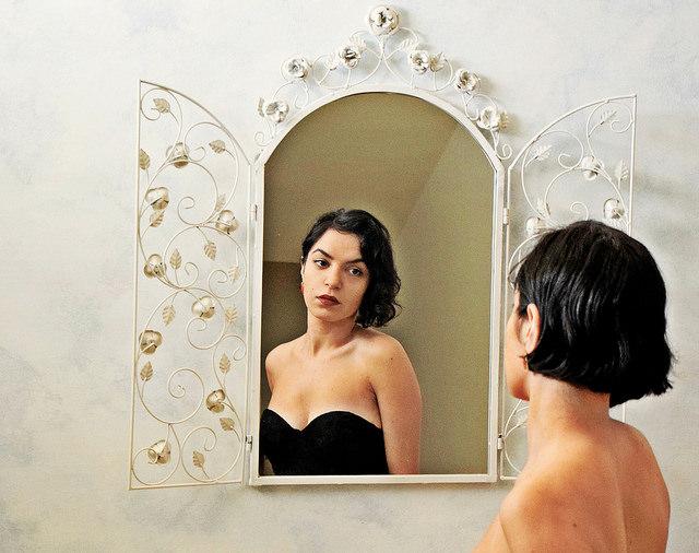 Une jeune femme se regarde dans un miroir.