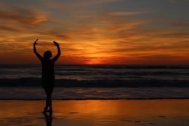 Photographie d'un coucher de soleil avec une personne qui danse sur la plage.