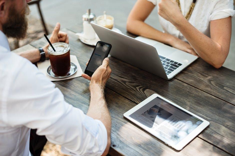 Deux personnes discutent à la terrasse d'un café, devant un ordinateur et un mobile.