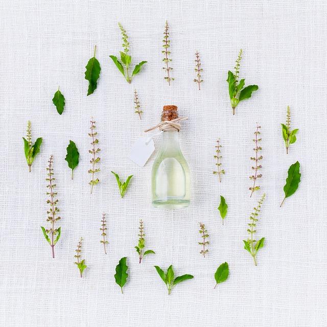 Bouquet de plantes entourant une fiole d'huile essentielle.
