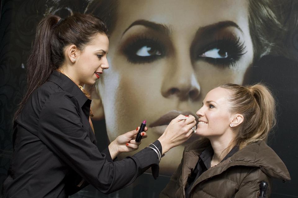 Une femme en train de se faire maquillée par une autre femme