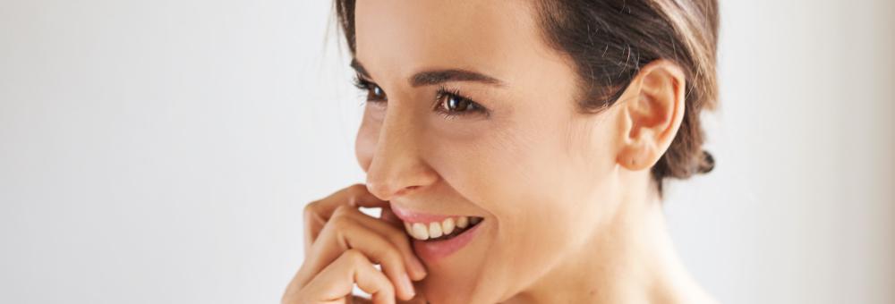 Femme souriante au visage lisse après une injection de botox.