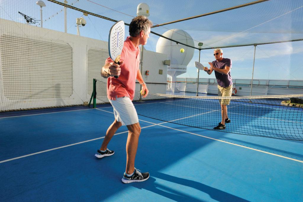 Deux hommes jouant au paddle-tennis sur un bateau de croisière.