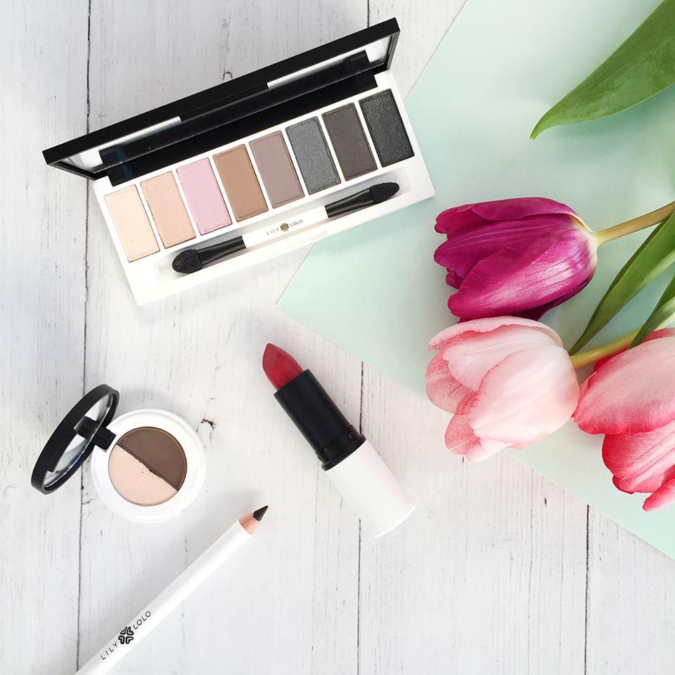 Maquillage Lily Lolo posé sur une table avec des fleurs.