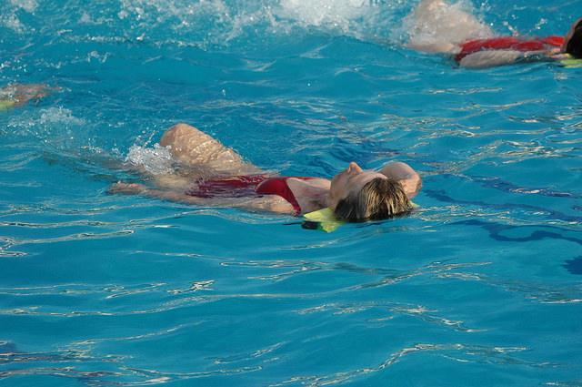 Femme en train de nager dans une piscine.