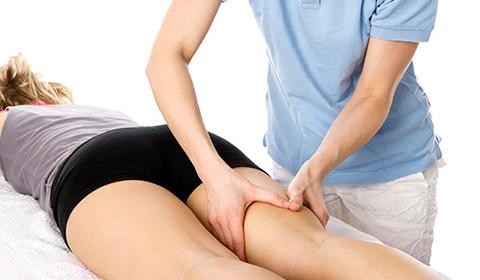 Personne en train de masser la jambe d'une patiente pendant la rééducation.