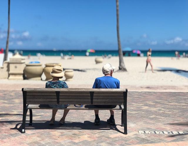 Personnes âgées face à la mer assis sur un banc.