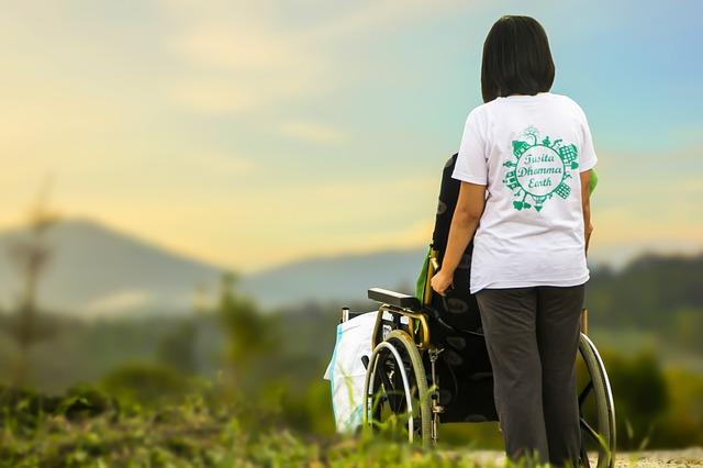Aide-soignante accompagnant une personne âgée en maison de retraite.