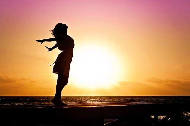 Femme épanouie à contre-jour d'un lever de soleil.