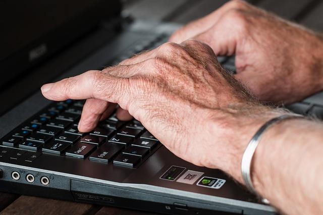 Une personne âgée tape au clavier.
