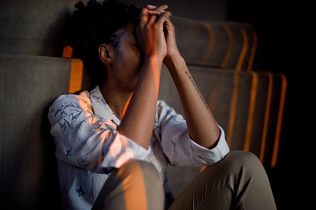 Jeune femme assise qui se tient la tête dans les mains.