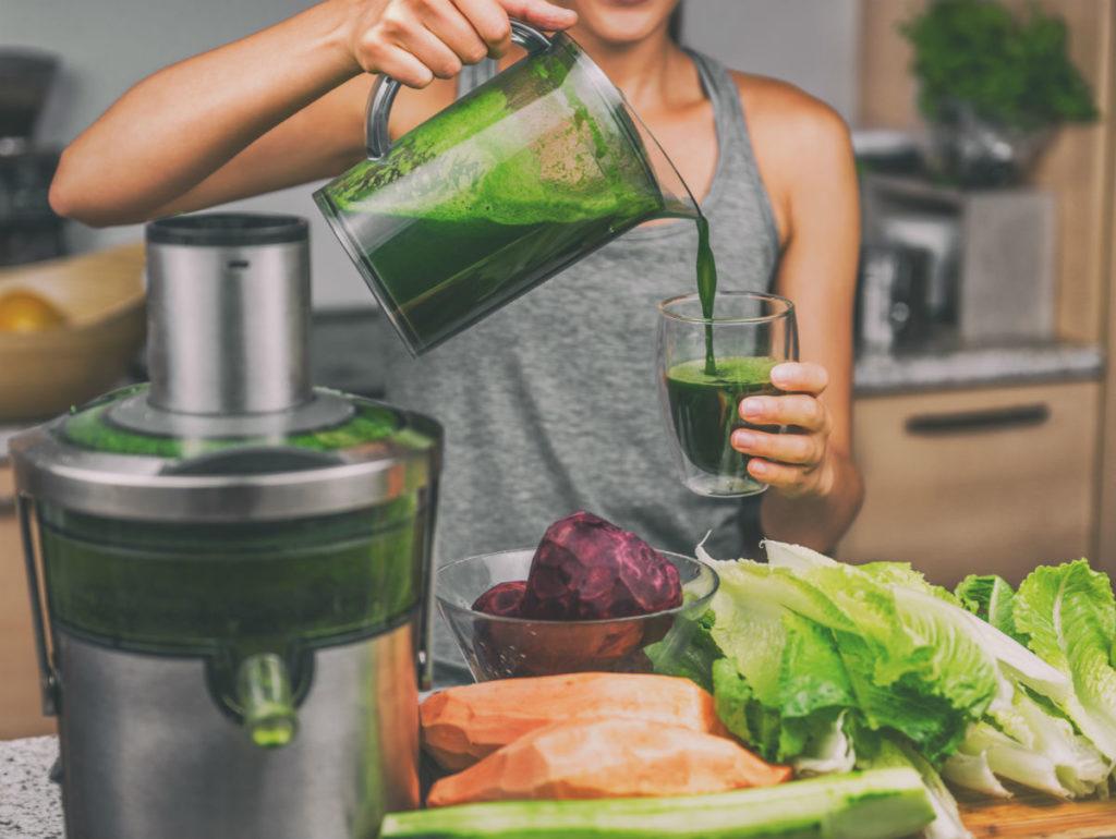 Personne en train de préparer un jus de fruits et légumes.