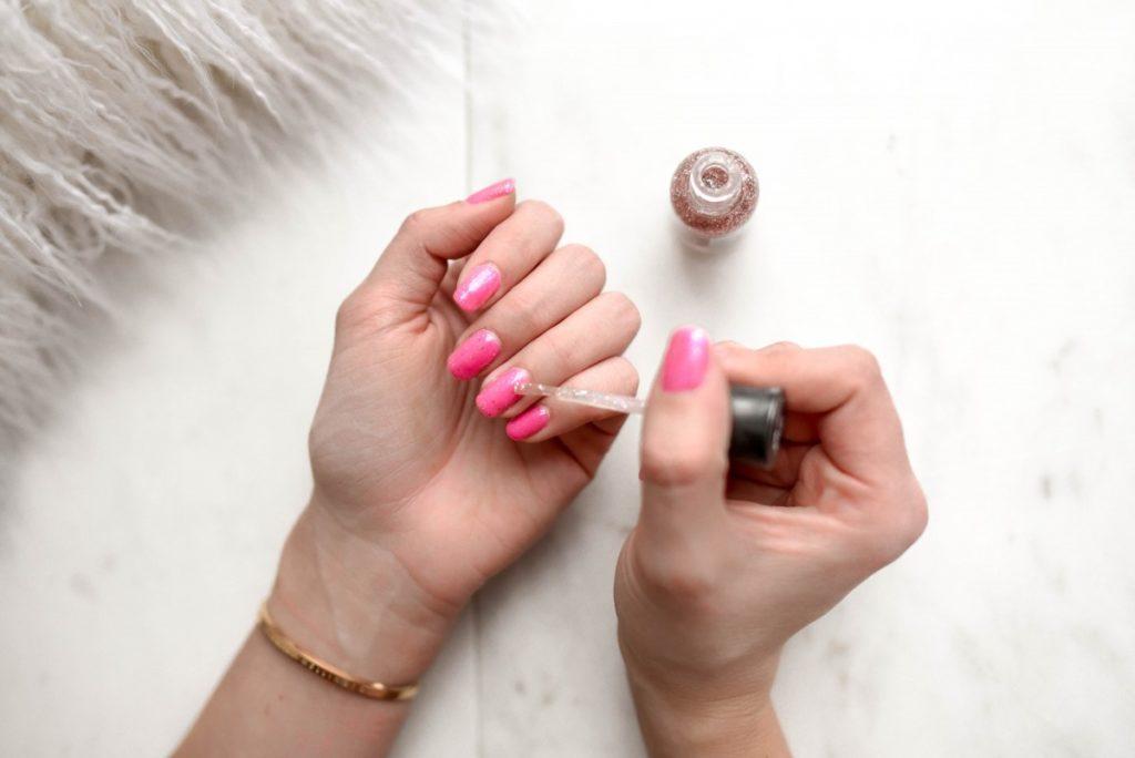 Femme en train de mettre du vernis sur ses ongles.