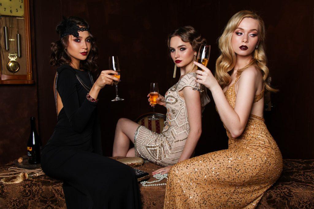 Ce sont trois femmes très apprêtées en robe de soirée qui boivent une coupe de champagne.