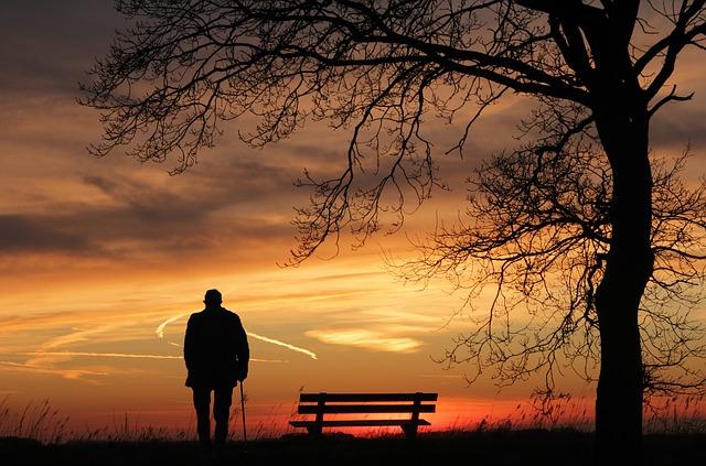 Personne âgée devant un coucher de soleil.