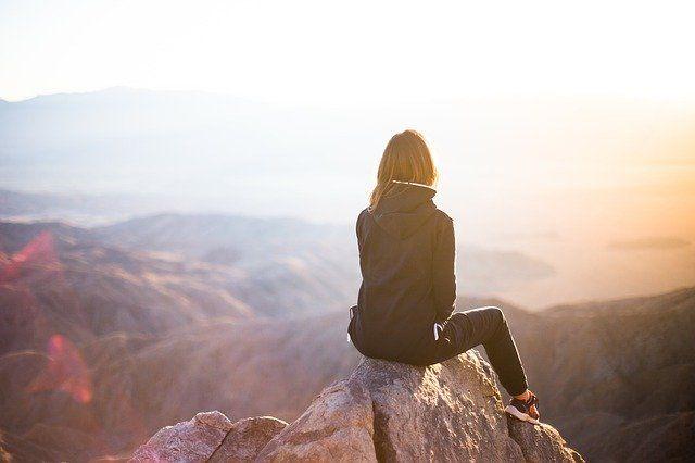 C'est une femme assise sur le sommet d'une montagne.