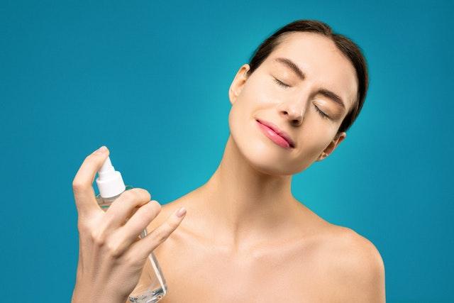 Femme se vaporisant de l'eau thermale sur le visage.