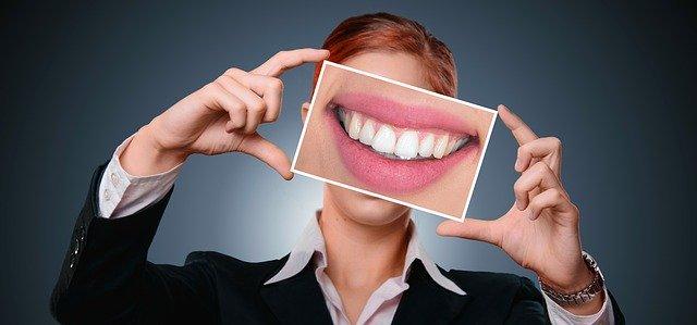 Femme avec photo d'une belle dentition devant le visage