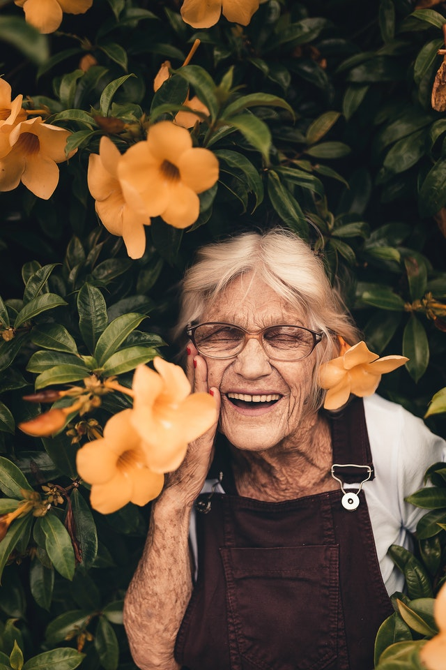 Vieille femme qui sourit dans des fleurs.