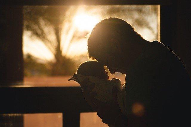 Père qui tient son bébé proche de son visage.