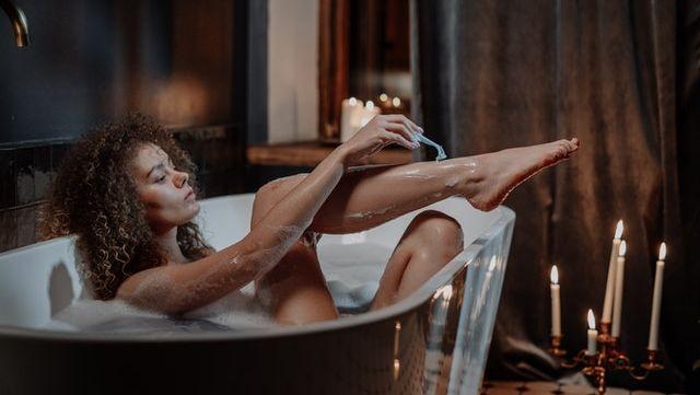 Une femme qui se rase dans un bain.