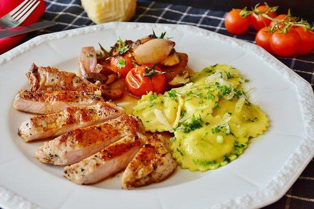 Assiette avec du poulet, des légumes et des ravioles