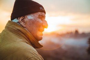 Homme âgé souriant en regardant l'horizon.